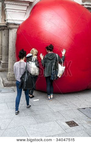 Three young ladies interact with Kurt Perschke's giant Red Ball that was squeezed into the entrance