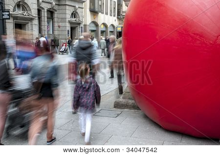 Passersby look at Kurt Perschke's giant Red Ball that was squeezed into the entrance of the Guildha