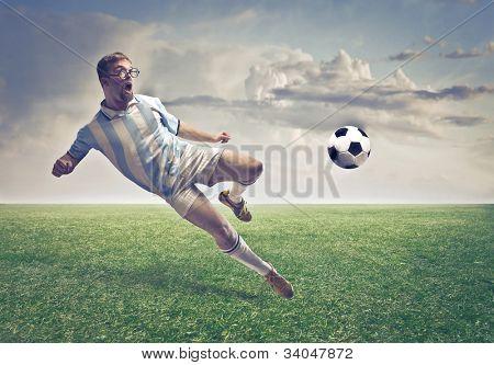 Soccer player shooting a ball on a football court