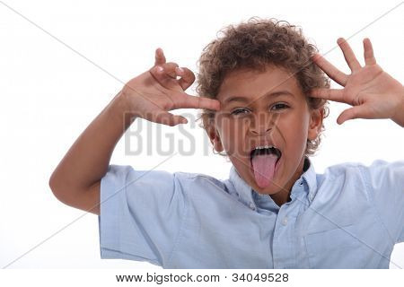 Young boy pulling a face and sticking his tongue out