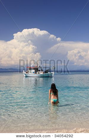 Young woman in the sea with fishing boat