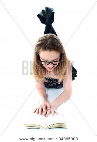 Little Girl With Book Lying On Floor