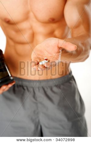 Close up of muscular man torso with hand full of pills on white