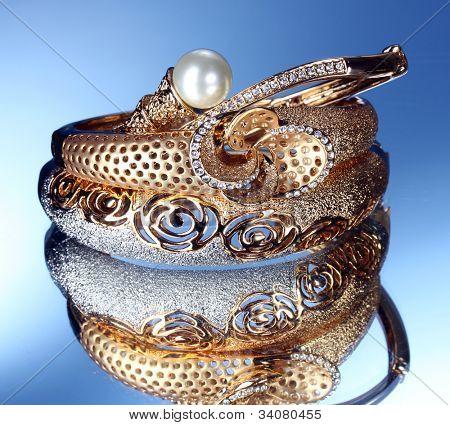 Beautiful gold bracelets on blue background