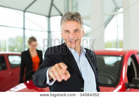 Mature single man with red auto in light car dealership with a female customer, a young woman, he is obviously buying a car or is a car dealer