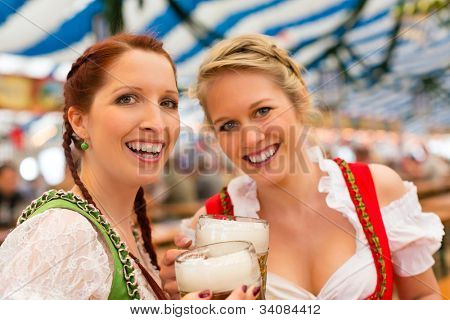 Young women in traditional Bavarian clothes - dirndl or tracht - on a festival or Oktoberfest in a beer tent