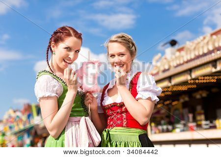 Young women in traditional Bavarian clothes - dirndl or tracht - with candyfloss on a festival or Oktoberfest