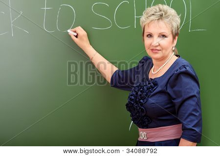 Portrait of a smiling teacher writing on a blackboard.