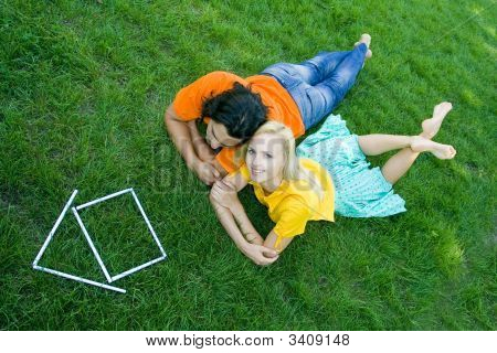 Couple Lying On Grass With Model House