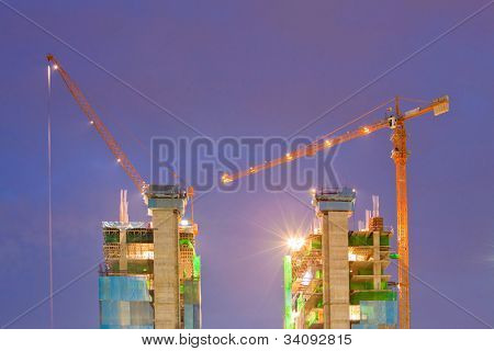 Big Construction Site with Working Cranes at dusk for Business Background