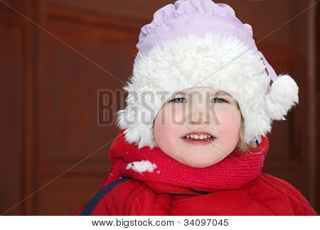 Cute Little Girl Wearing Warm Clothing Stands And Looks At Camera