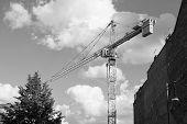 Site Under Construction. Construction Crane On Cloudy Sky. Crane For Building Construction. Construc poster