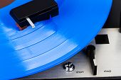 Close Up Of Turntable Cartridge On A Vinyl Record. Turntable Playing Vinyl. Needle On Rotating Blue  poster