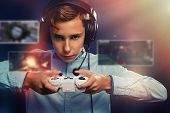 The Concept Of Video Games. A Teenage Boy, In Headphones With A Serious Look Playing A Game. In The  poster
