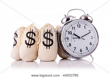 Sacks of money and alarm clock on white