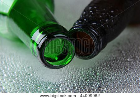 Closeup of two beer bottles on a wet stainless steel surface. One bottle is green the other brown. Shallow depth of field as the open neck of the bottles points forward.