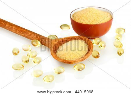 Gelatin in a bowl and wooden spoon on white background close-up