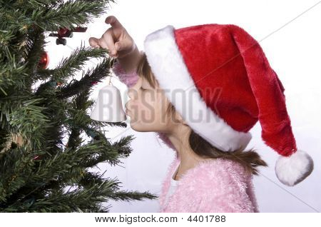 Girl In Santa Hat Kisses A Bell Ornament.
