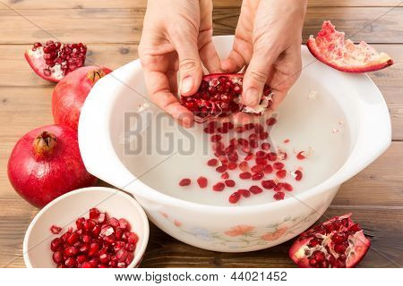 Hands seeding a pomegranate with the water method