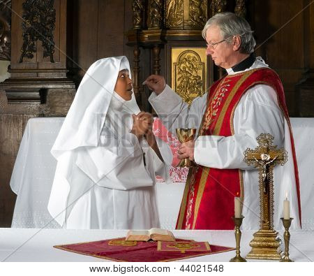 Catholic priest giving holy communion to a nun