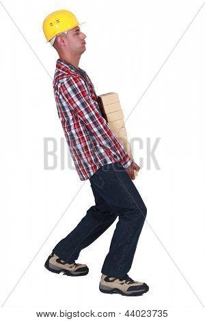 Mason carrying pile of bricks