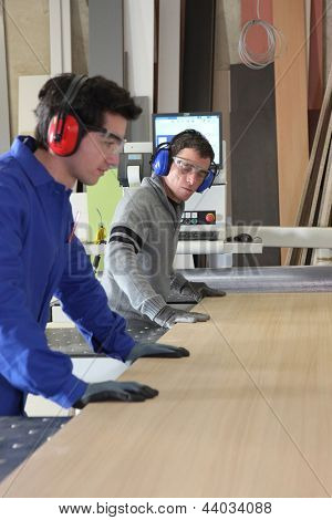 Two workers using factory saw