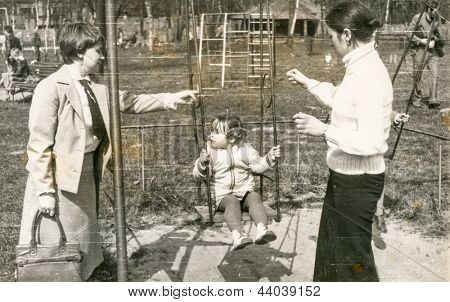 Vintage photo of mother, aunt and daughter on swing (seventies)