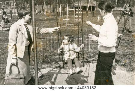 Vintage Foto von Mutter, Tante und Tochter auf Schaukel (70er-Jahre)