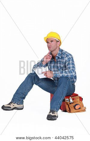 Builder sat on tool box thinking