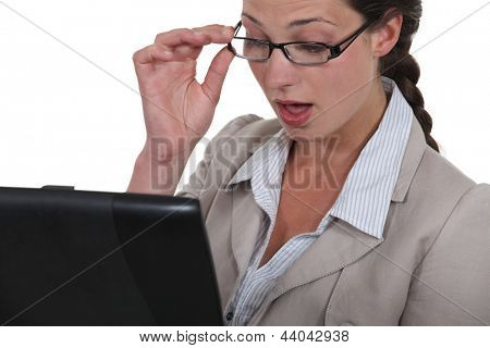 Woman looking in surprise at her laptop