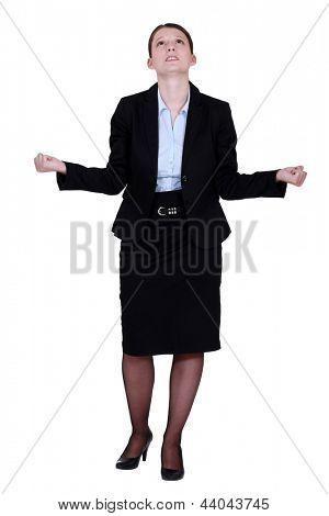 young businesswoman looking upwards tight-fisted