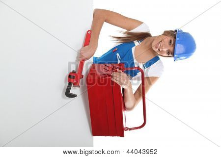 craftswoman holding a spanner and a tool box