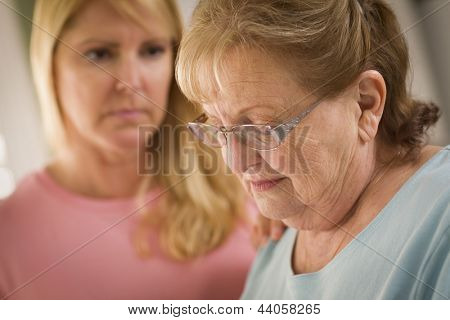 Young Adult Woman Consoles Sad Senior Adult Female.