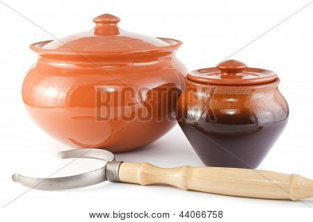 clay pots of the different size and the oven fork on a white background