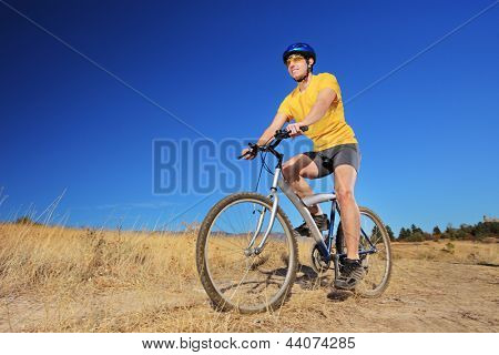 A young male with yellow shirt and helmet riding a mountain bike outdoors