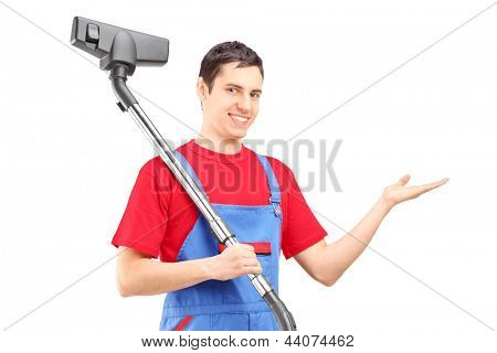 A young man with a vacuum cleaner gesturing with his hand isolated on white background