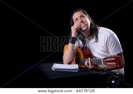 Músico Guitarrista escribir una canción con su guitarra
