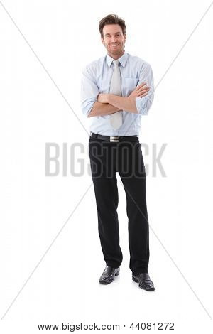 Confident businessman standing arms crossed, smiling.