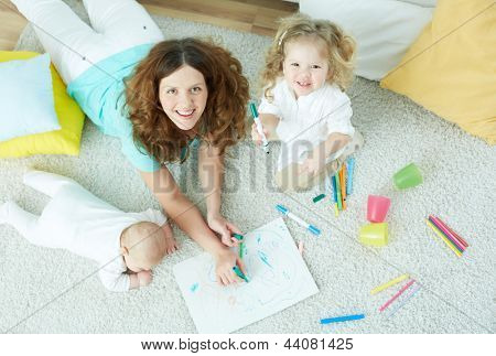 The above-view portrait of a beautiful babysitter looking after cute kids