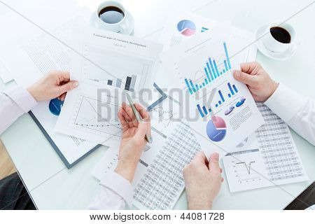 Above angle of mature businesspartners hands during discussion of papers