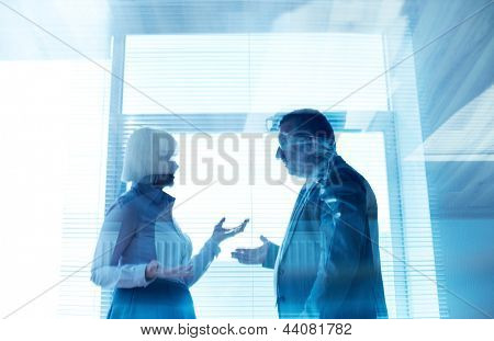 Outlines of mature businessman and his colleague communicating by the window in office