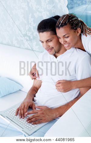 Image of young guy and his girlfriend working with laptop at home