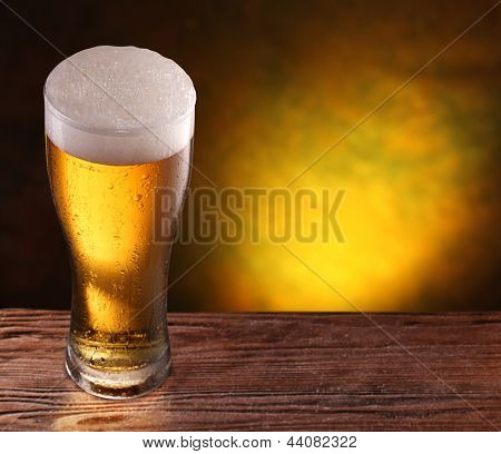 Beer glass on a wooden table. Copyspace. Dark yellow background.