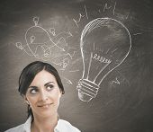 stock photo of lightbulb  - Concept of a businesswoman with a big idea - JPG