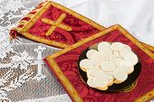 Red vestment set and communion hosts on a golden plate