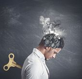 stock photo of fatigue  - Concept of stress with gear in the head of a businessman - JPG