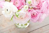 stock photo of buttercup  - Bouquet of pink ranunculus in vase on wooden background - JPG