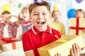 Joyful boy with giftbox looking at camera with his friends on background