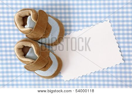 Baby shoes and blank note on blue background