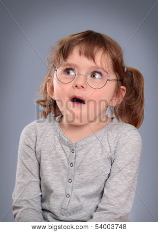 Fanny little girl with glasses on grey background
